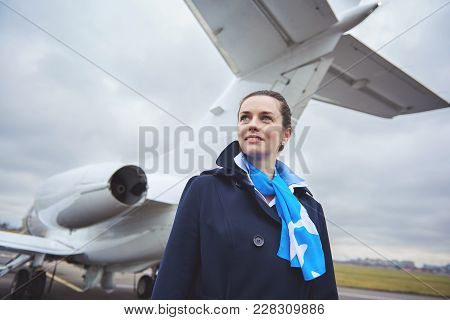 Portrait Of Stewardess Expressing Happiness While Standing Near Aircraft On Street. Occupation Conce