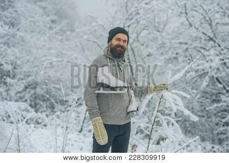 Bearded Man With Skates In Snowy Forest. Man In Thermal Jacket, Beard Warm In Winter. Skincare And B