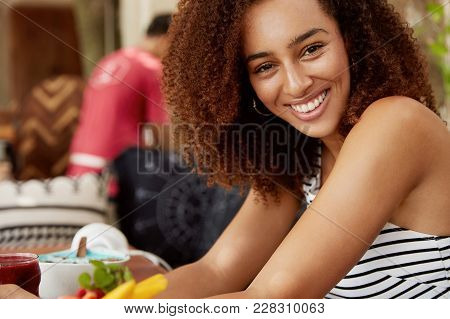 Positive Curly Young Woman With Dark Healthy Skin, Smiles Pleasantly, Sits At Cafe Table Surrounded