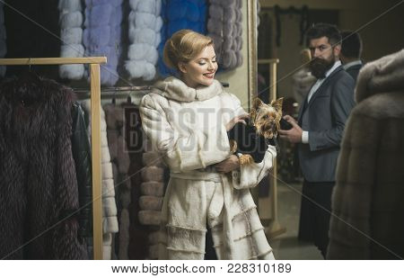 Man With Strict Face And Woman With Coats In Fur Shop. Money And Style Concept. Woman In Fur Coat Wi