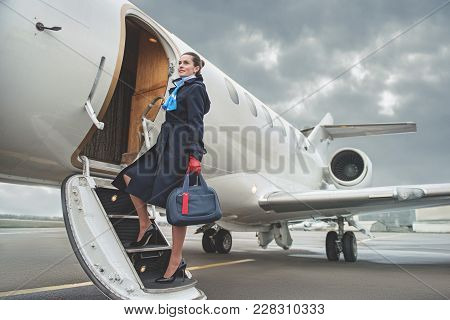Full Length Portrait Of Cheerful Young Air-hostess Entering Airplane While Holding Baggage. Job Conc