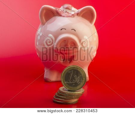 Piggy Bank And One Euro On A Pile Of Coins. Red Background. Cover. Euro Money.  Currency Of The Euro