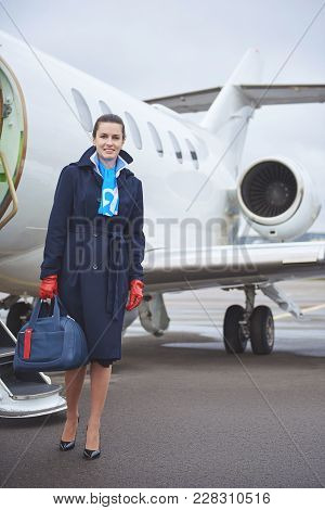 Full Length Portrait Of Beaming Stewardess Holding Bag While Standing Near Aircraft Outdoor. Job Con