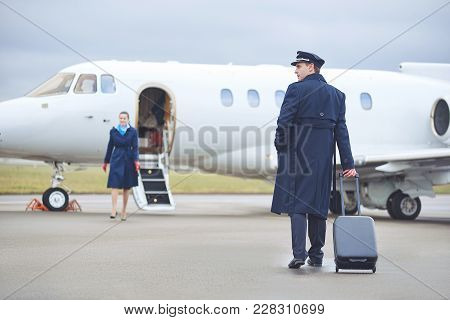 Full Length Side View Smiling Aviator Keeping Luggage While Moving To Airplane. Happy Stewardess Goi