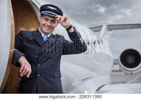 Portrait Of Happy Aviator Locating Near Aircraft. He Looking At Camera. Profession Concept