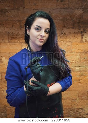Portrait Of Beautiful Brunette Girl With Tattoo Machine, Looking At The Camera. Artist In Leather Ap