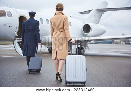 Full Length Girl And Aviator Keeping Luggages While Going To Plain. They Turning Back To Camera. Jou