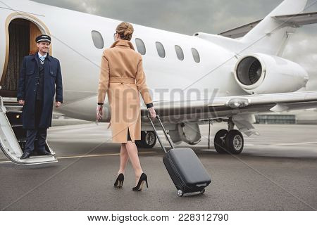 Full Length Young Woman With Luggage Moving To Plane. Outgoing Aviator Looking At Her While Sanding