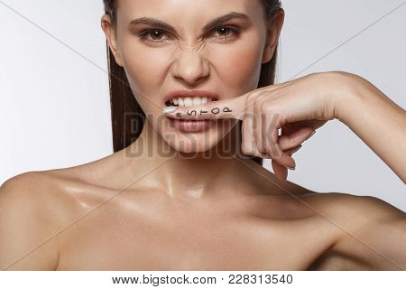 Portrait Of Aggressive Girl Biting Her Finger While Looking Forward With Irritation. Stop Lettering.