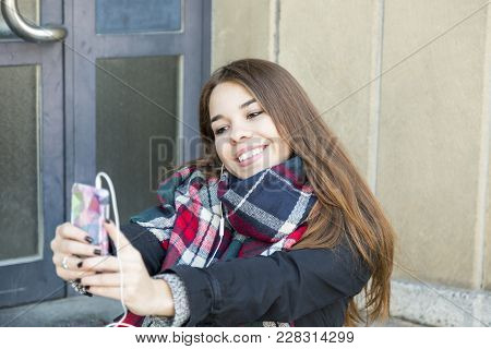 Pretty Vivacious Young Female Student In A Trendy Warm Scarf Taking A Selfie On Her Mobile Phone Gri
