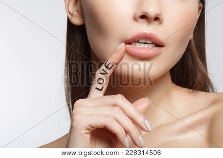 Close Up Of Affectionate Young Woman Touching Her Lips With Desire. Love Concept. Isolated And Copy