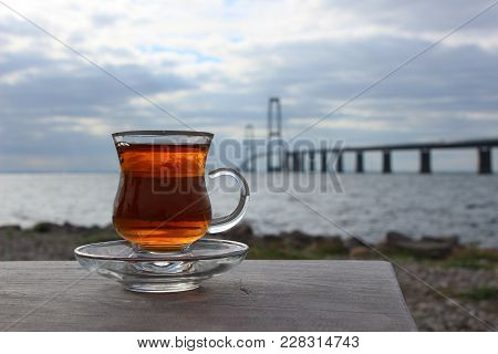 Danish Great Belt Bridge And Hot Tea. Photo Of The Bridge And Landscape. A Glas Of Hot Tea. Bridge A