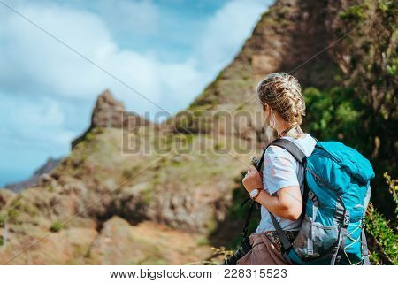Woman With Camera And Backpack In Front Of The Arid Fins Of Rocks On Santo Antao Island, Cabo Verde.