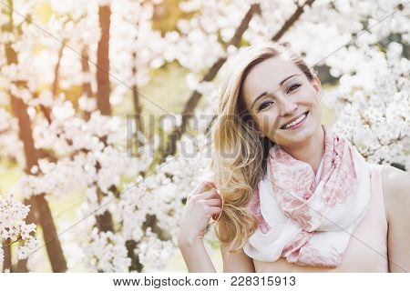 Close Up Of Beautiful Blond Woman Looking Up And Smiling Underneath Tree Branches Filled With White