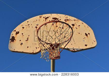 A Rusty Basketball Hoop And Backboard Against A Deep Blue Sky