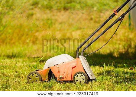 Gardening, Garden Service. Old Lawn Mower Cutting Green Grass In Backyard. Mowing Field With Lawnmow