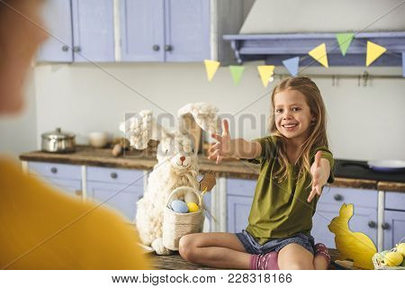 Portrait Of Jolly Female Child Sitting On Kitchen Table With Big Easter Rabbit Toy, She Is Reaching