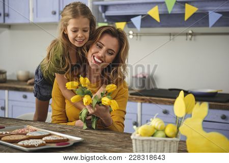 Portrait Of Cheerful Attractive Woman With Flowers Sitting In Kitchen With Her Daughter. Girl Is Hug