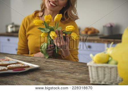 Joyful Young Woman Sitting At Kitchen Table And Holding Beautiful Yellow Flowers. Glazed Cookies And