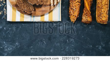 Half View Of Sliced Dark Bread On Wooden Plate With Napkin And Other Pastry, Rye Laid In Row Isolate