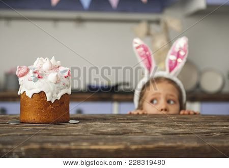 Cute Little Sweet Tooth In Bunny Ears Headband Peeking Out From Behind Kitchen Table And Looking At