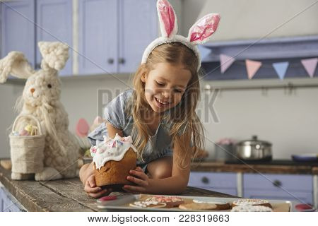 Cheerful Little Girl In Cute Bunny Ears Headband Sitting On Kitchen Bar Table With Easter Cake And L
