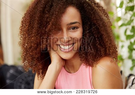 Close Up Shot Of Positive Dark Skinned Teenage Girl Has Afro Hairstyle, Dressed Casually, Has Shinin