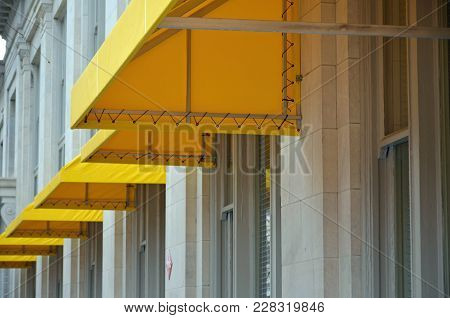 Yellow Canopies Pop Out On White Building