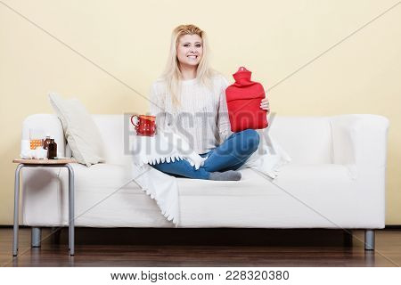 Happy Woman Showing Ways To Get Rid Of Fever Holding Hot Water Bottle And Hot Drink In Mug Sitting,