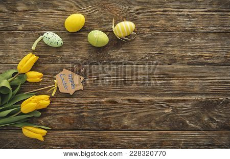 Top View Of Bunch Of Spring Flowers And Colored Eggs On The Timbered Table. Copy Space In Right Side