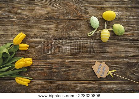 Top View Of Yellow Tulips And Faberge Eggs Lying On The Wooden Table