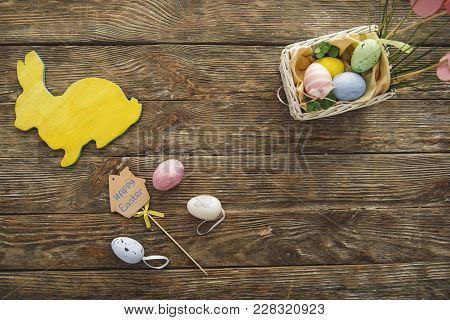 Top View Of Yellow Rabbit And Box With Tinted Eggs On The Timbered Panel