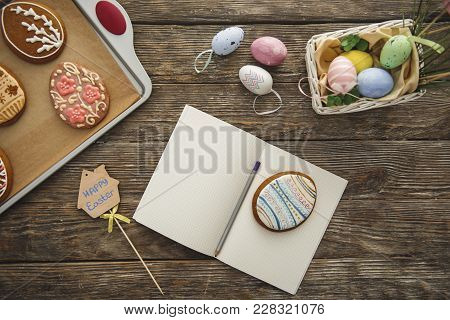 Top View Close Up Of Easter Decorations And Opened Exercise Book With Pen And Egg Shaped Cookie On I
