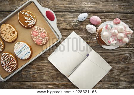Top View Close Up Of Sweet Bakery Products, Eggs And Opened Copybook On The Wooden Table