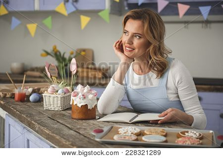 Pensive Woman Relaxing On Weekend. She Is Sitting In The Decorated Cuisine And Looking Aside. Easter