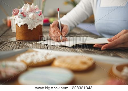 Close Up Of Female Hand Making Notes With Pencil In Copybook. Easter Bread Is On The Table