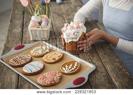 Close Up Of Female Hands Touching Traditional Easter Bread. Cookies And Colored Eggs Standing Nearby