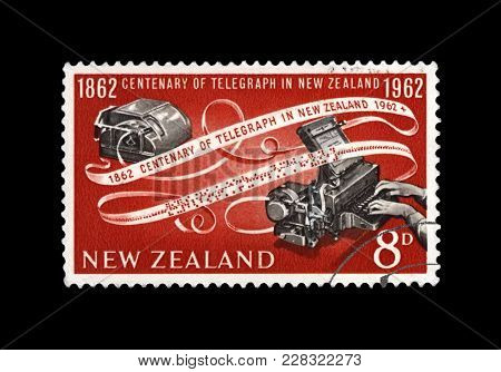 NEW ZEALAND - CIRCA 1962: canceled stamp printed in New Zealand shows telegraph device and encoded paper tape, 100th anniversary of inauguration of the telegraph in New Zealand, circa 1962. vintage postal stamp isolated on black background.