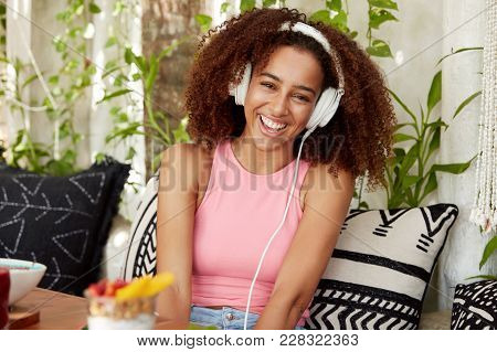 Happy Female With Dark Healthy Skin, Listens Anecdotes Online With Special Application And Headphone