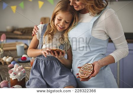 Satisfied Mother And Daughter Embracing And Admiring Their Handmade Confection Indoors