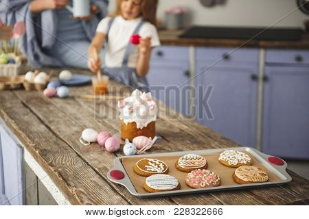 Traditional Easter Bakery Standing On The Dining Table. Mom And Daughter Standing On Background