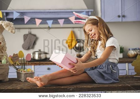 Satisfied Kid Admiring The Gift Box On Holiday While Sitting On The Cuisine Table