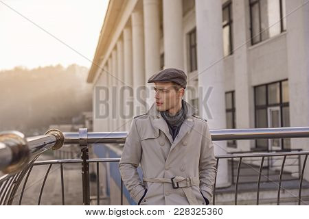 Serious Young Trendy Man Is Standing Outdoors While Leaning On Handrails. He Is Looking Aside With C