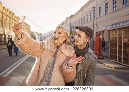 Say Cheese. Cheerful Young Couple Making Selfie Using Mobile Phone And Standing On Street. Girl Is H
