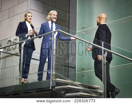 Senior Corporate Executive Welcoming Visitor On Stair Of Modern Office Building, Low Angle View.