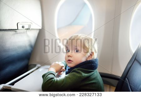 Charming Kid Traveling By An Airplane. Afraid Little Boy Sitting By Aircraft Window During The Fligh