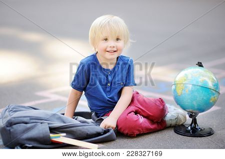 Cute Blond Boy Doing Homework Sitting On School Yard After School With Bags Laying Near. Back To Sch