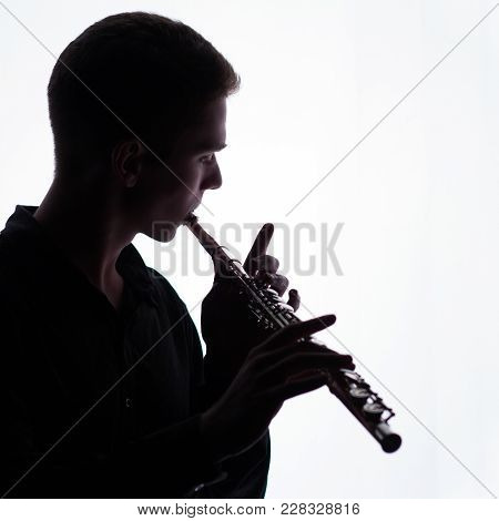 A Young Man Is Playing The Flute. Silhouette. A Square Picture. Copy Space.