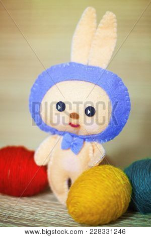 Easter Bunny Toy With Color Eggs In The Chaff Background. Red, Yellow And Green Eggs. Background Blu