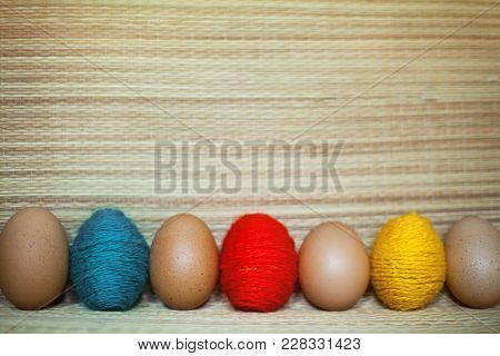 Red, Yellow, Green And Pure Brown Eggs In The Straw Background. Eggs Are Threaded In Colored Thread
